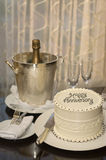 Happy Anniversary. Cake decorated with Happy Anniversary on a table with Champagne bucket, two champagne flutes, Champagne bottle and silverware royalty free stock photos