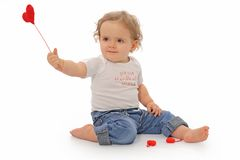 Happy anniversary. Lovely one year old girl playing with red hearts royalty free stock photos