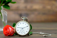 Happy Anniversary card with bouquet of red roses and pocket watch. On wooden background Stock Photography