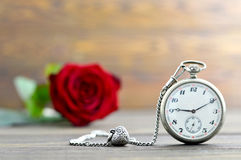 Happy Anniversary card with pocket watch, heart pendant and red rose. On wooden background Royalty Free Stock Photo