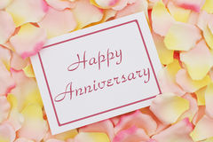 Happy Anniversary card. A white card with text Happy Anniversary and a pink and yellow rose pedal backgrounds Royalty Free Stock Photography