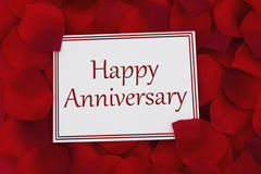Happy Anniversary Card. A white card with text Happy Anniversary and a red rose petal backgrounds Royalty Free Stock Photography