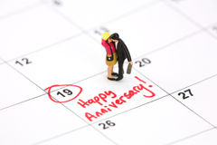 Happy Anniversary Concept. Concept image of a miniature couple kissing on a calendar that has been marked in red with Happy Anniversary. Taken with a Canon 5D Stock Images