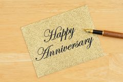 Happy Anniversary greeting card on gold greeting card with pen on textured wood royalty free stock photo