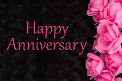 Happy Anniversary greeting with pink roses on black. Rose textured plush fabric stock photo
