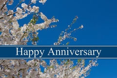 Happy Anniversary Greeting. A tree in full bloom with blue sky and text Happy  Anniversary Royalty Free Stock Photo