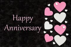 Happy Anniversary greeting with white and pink hearts with candy hearts on black stock illustration