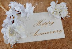 Happy Anniversary. Horizontal image of a parchment card with white and ivory colored silk floral decorations on burlap with a message of Happy Anniversary stock photos