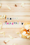 Happy Anniversary. Letters Cut out from Magazine With Peony on Wooden Background Stock Images