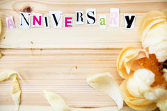 Happy Anniversary. Letters Cut out from Magazine With Peony on Wooden Background Stock Photography