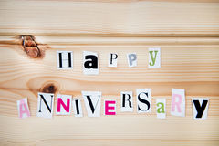 Happy Anniversary. Happy  Anniversary Letters Cut out from Magazine on Wooden Background Royalty Free Stock Images
