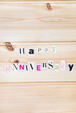 Happy Anniversary. Happy  Anniversary Letters Cut out from Magazine on Wooden Background Royalty Free Stock Photos