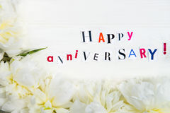 Happy Anniversary Letters Cut out from Magazines and White Peoni. Es nearby, white background Royalty Free Stock Image
