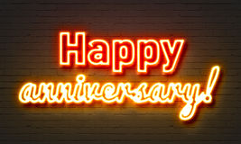 Happy anniversary neon sign on brick wall background. Stock Image