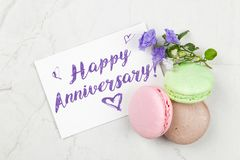 Happy anniversary postcard. Writing a Happy Anniversary postcard on white marble table stock image