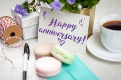 Happy anniversary postcard. Writing a Happy Anniversary postcard on white marble table royalty free stock images