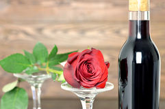 Happy Anniversary: Red rose, two wine glasses and bottle of red wine on wooden background. Happy Anniversary: Red rose, wine glasses and bottle of red wine on Royalty Free Stock Photos