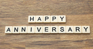 Happy Anniversary. The word happy anniversary written in tiles on a wooden surface Royalty Free Stock Photography