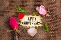 Happy anniversary written in hole on the burlap. With rose flowers and wooden red heart stock images