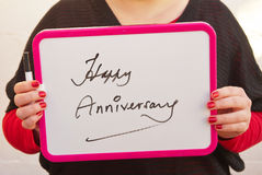 Happy Anniversary. Young woman holding white chalkboard with purple edges and text message saying ' Happy Anniversary Royalty Free Stock Image