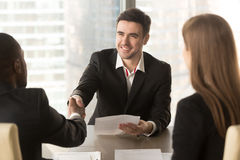 Happy applicant greeting employer, partners handshaking, success. Happy applicant greeting employers at job interview, cheerful satisfied partners shaking hands Royalty Free Stock Photography