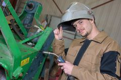 Happy apprentice welder at work in plant Royalty Free Stock Image
