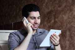 Happy arab businessman with phone and tablet Royalty Free Stock Photography