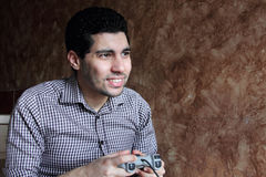Happy arab egyptian businessman playing playstation. Image of arabian egyptian business man wearing shirt and feeling happy while playing playstation Royalty Free Stock Image