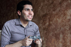 Happy arab egyptian businessman playing playstation. Image of arabian egyptian business man wearing shirt and feeling happy while playing playstation Royalty Free Stock Photos