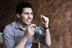 Happy arab egyptian businessman playing playstation. Image of arabian egyptian young man wearing shirt and feeling happy while playing playstation Royalty Free Stock Image