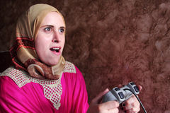Happy arab egyptian muslim woman playing playstation. Image of arabian egyptian muslim woman wearing hijab and feeling happy while playing playstation Royalty Free Stock Image