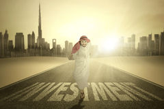 Happy Arab man runs with Investment word. Portrait of Arabic entrepreneur running on the road with Investment word while smiling at the camera Stock Photo