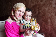 Happy arab muslim mother with her baby girl with ramadan lantern royalty free stock images