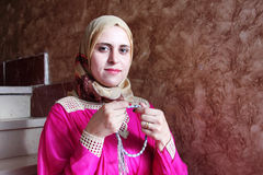 Happy arab muslim woman asking allah with rosary. Arabian egyptian muslim woman asking allah and searching hope with rosary in hand Royalty Free Stock Photo