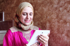 Happy arab muslim woman with tablet. Photo of arabian egyptian muslim woman feeling happy while looking at tablet Stock Photos