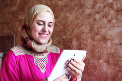 Happy arab muslim woman with tablet. Photo of arabian egyptian muslim woman feeling happy while looking at tablet Royalty Free Stock Photo