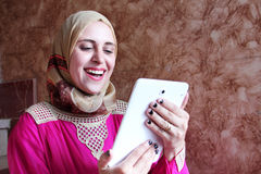 Happy arab muslim woman with tablet. Photo of arabian egyptian muslim woman feeling happy while looking at tablet Stock Images