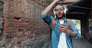 Happy Arab tourist in headphones listening to music singing dancing outdoors. Having fun alone in the street holding smartphone. Youth culture and devices stock video footage