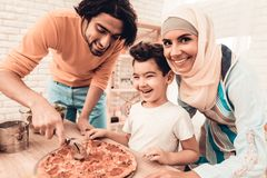 Happy Arabian Family Eating Pizza in Kitchen. Muslim Family. Smiling Boy. Young Arabian Woman. Modern Kitchen at Home. Man Using Kitchenware. Young Family royalty free stock photos