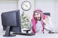 Happy arabian man looking money. Happy arabian businessman looking much money out of computer while sitting on the chair Stock Images