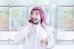 Happy Arabian man speaking on cellphone Stock Photo