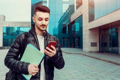 Arabian student using smartphone outside. Smiling man looks at phone in front of modern building after classes stock photography