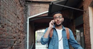 Happy Arabian tourist talking on mobile phone laughing standing outdoors. Happy Arabian tourist is talking on mobile phone laughing standing outdoors in city stock footage