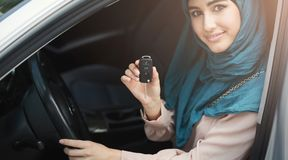 Happy arabian woman holding car key in new vehicle. Happy arabian woman holding car key inside new vehicle, copy space Stock Image