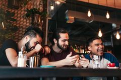Happy arabian young men hanging in loft cafe. Group of mixed race people having fun in lounge bar stock image