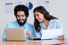 Happy arabic business team at work at desk stock image