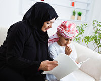 Happy Arabic child at home with his mother Stock Photos