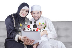 Happy Arabic family shopping online on tablet royalty free stock images