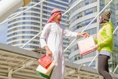 Arabic men shopping. Happy Arabic men with city shopping hand holding paper bags royalty free stock photos