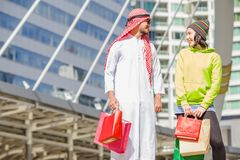 Arabic men shopping. Happy Arabic men with city shopping hand holding paper bags stock photo